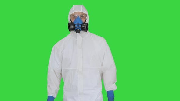 Virologist Man in Protective Costume Checking the Situation on a Green Screen, Chroma Key.