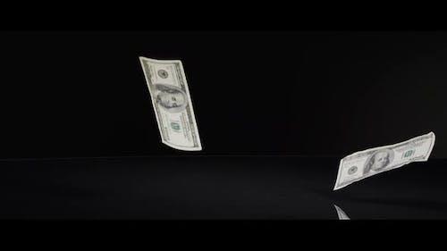 American $100 Bills Falling onto a Reflective Surface - MONEY 0012