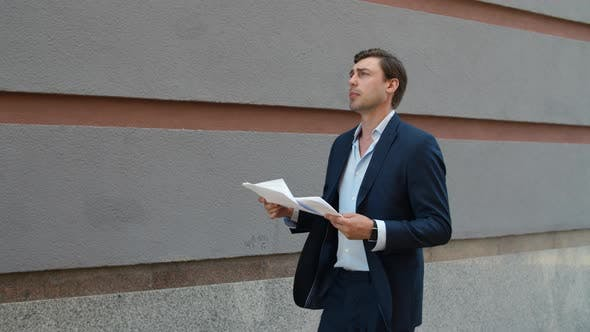 Thumbnail for Serious Business Man Reading Documents. Man Walking with Documents at Street