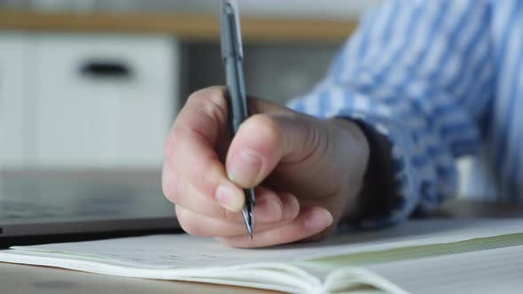 Close Up Of A Woman's Hand Holding A Pen And Writing Notes In A Notebook Sitting At Home