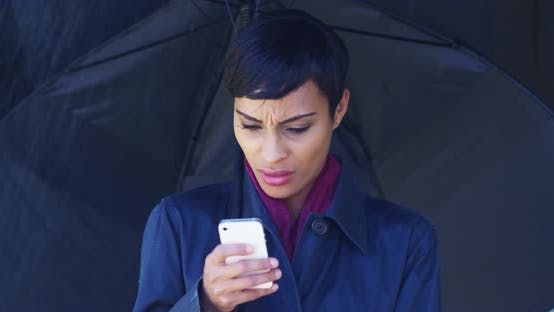 Thumbnail for Black woman with umbrella standing in rain using mobile phone