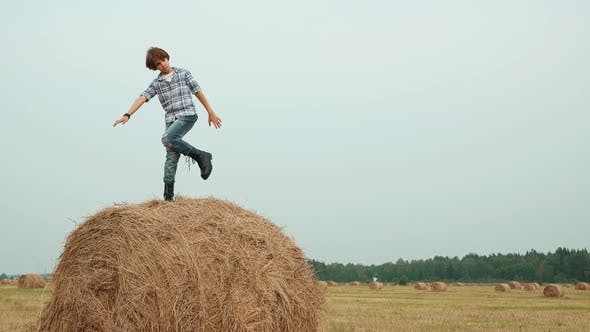 Thumbnail for Stylish Teenage Boy Posing on Haystack in Field