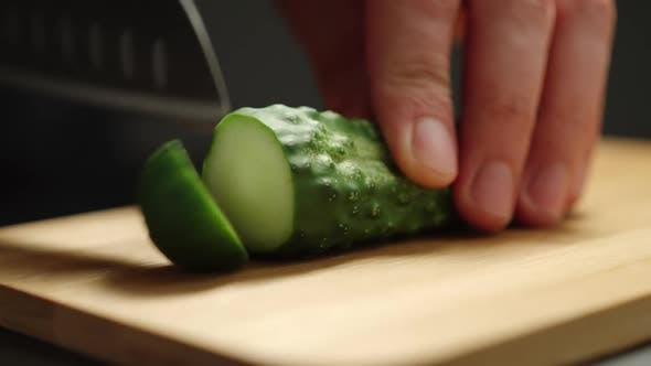 Man Cutting A Fresh Cucumber On Wooden Board