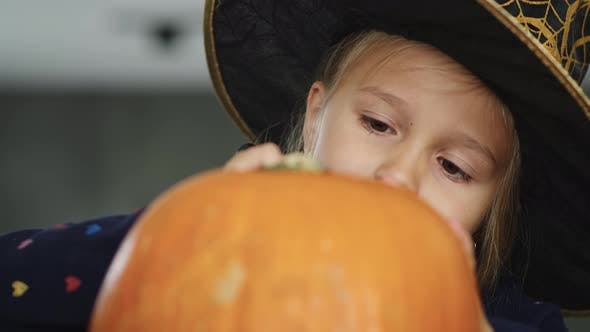 Thumbnail for Little girl in witch costume drawing on pumpkin