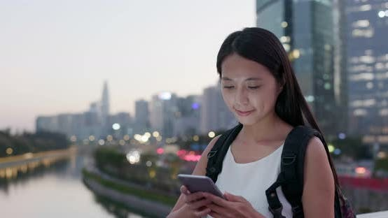 Thumbnail for Woman work on mobile phone in city at evening time