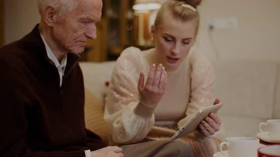 Senior Man Talking While Granddaughter Holding Digital Tablet At Home