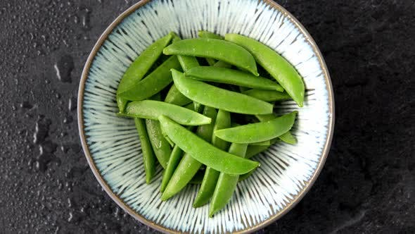 Plate of Peas on Wet Slate Stone Background