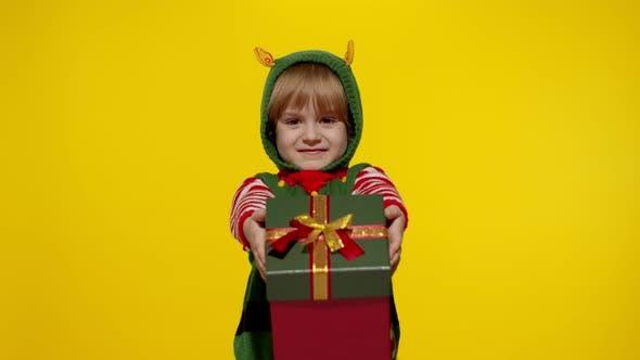Thumbnail for Kid Girl Christmas Elf Santa Helper Giving Present Gift Box To Camera