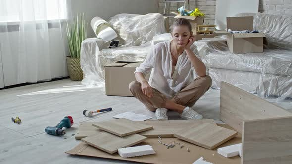 Thumbnail for Tired Woman Looking at Disassembled Furniture