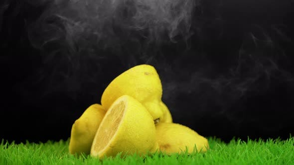 Thumbnail for Smoke falling over a rotating pile of lemons placed on nicely trimmed grass