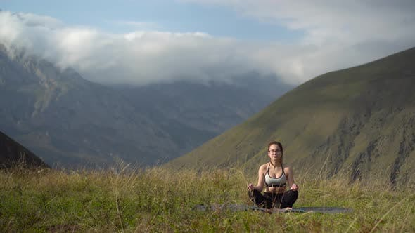 Young Woman in Tracksuit Practices Yoga Performing Lotus Position in the Mountains.