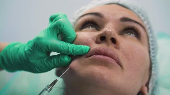 Cosmetologist Does Antiaging Filler Injection To Client