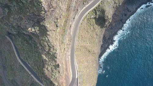 Aerial Drone Footage of an Empty Road Along a Cape with Vertical Overhanging Cliffs Over the Ocean
