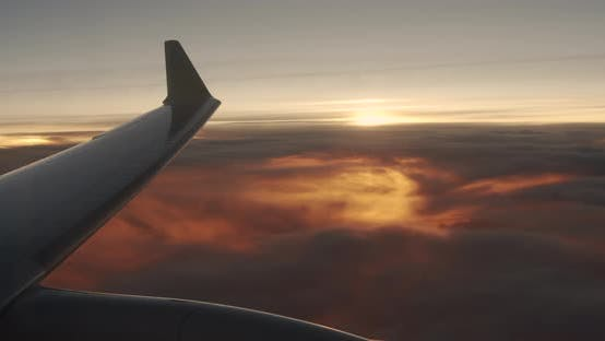 Thumbnail for Wing of an Airplane Flying Above the Clouds with Sunset Sky. View From the Window of the Plane.