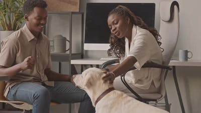 African American Couple Playing with Dog