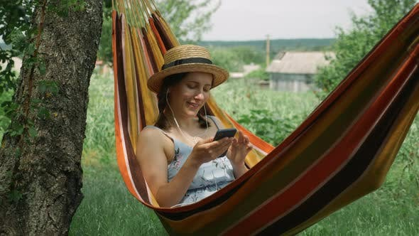 Thumbnail for Woman in earphones lying in hammock and listening to music, singing and relaxing at green garden