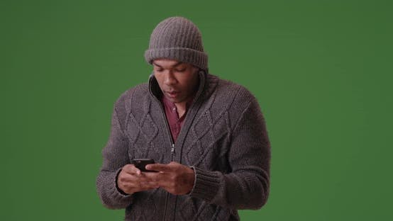 Thumbnail for An African American man stands trembling on his smart phone on green screen