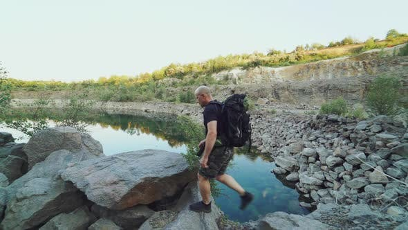 A tourist in summer clothes walks on the edge of a quarry with huge stones