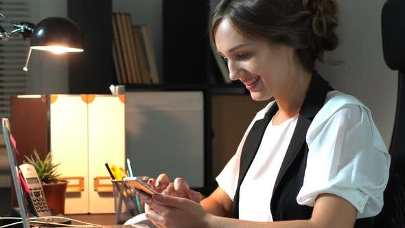 Thumbnail for Businesswoman Sitting At Her Workplace In Office And Use Smart Phone