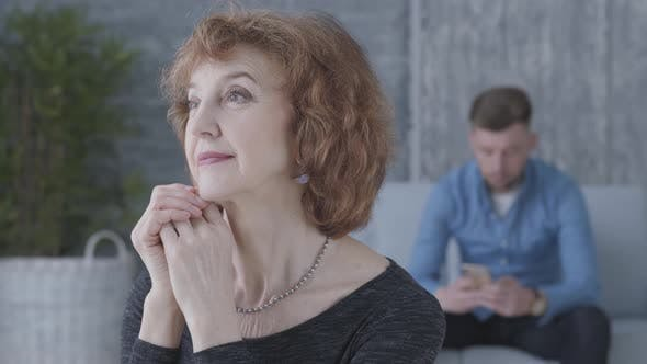 Thumbnail for Close Up Portrait of a Senior Mature Woman in the Foreground. The Blurred Figure of the Sad Unhappy