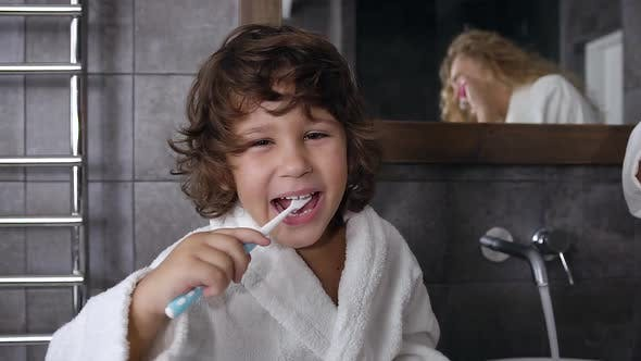 Cover Image for Little Boy with Dark Curly Hair Dressed in Robe Brushing His Teeth
