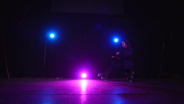 Professional Roller Skater Girl Crouches on Rear and Front Wheels in Scene, Approaching View of Pink