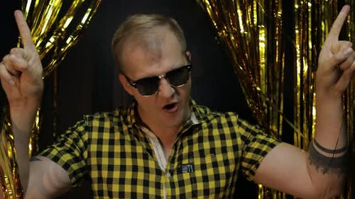 Portrait of Caucasian Man Posing on Black Background. Gold Shining Foil Strips. Party, Music, Disco
