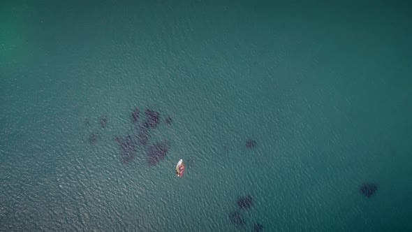 Thumbnail for Aerial view of windsurfer and boat in turquoise sea in Greece