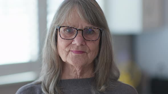 Thumbnail for Close up portrait of grey haired senior woman with glasses looking at camera