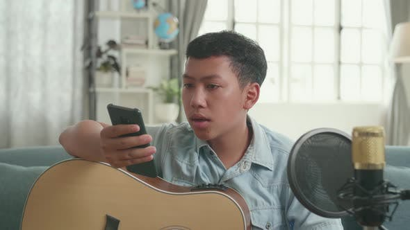 Asian Boy Vlogger With Guitar Read Comment On Mobile Phone While Streaming