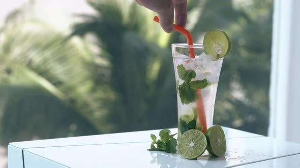 Man Hand Mixes Frozen Mojito with Ice Cubes and Lime Halves