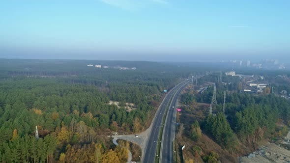 Aerial Drone Footage. Fly Over Autobahn Near Forest with Town on Horizon.