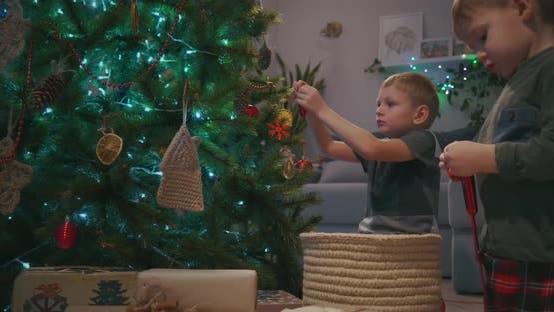 Thumbnail for Zwei Jungen schmücken Weihnachtsbaum Weihnachtsbaum im Wohnzimmer mit Weihnachtsspielzeug