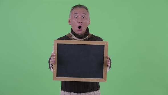 Thumbnail for Happy Mature Japanese Man Holding Blackboard and Looking Surprised