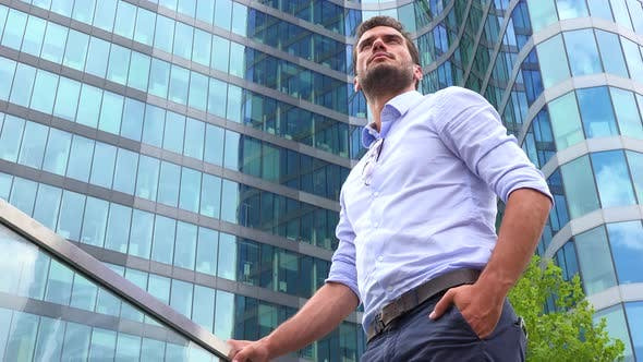 Thumbnail for A Businessman Stands in Front of an Office Building and Looks Around Proudly, Closeup From Below