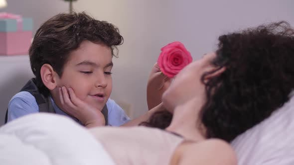 Boy Caressing Sleeping Mom's Face with Rose