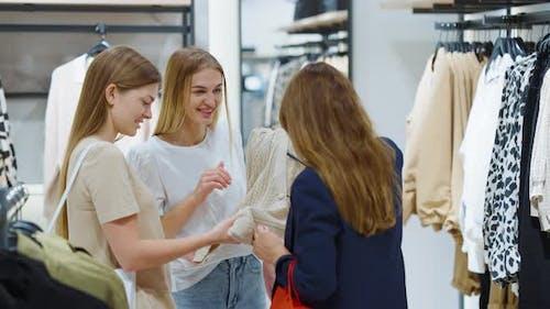 Female Friends Choosing Cardigan in Fashion Store Together