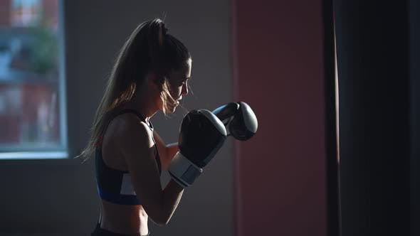White Female Athlete Boxing the Punching Bag in Urban Industrial Gym