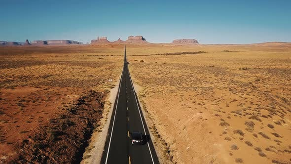 Thumbnail for Amazing Aerial Shot of Silver Car Driving Along Amazing American Sandstone Desert Highway Road in