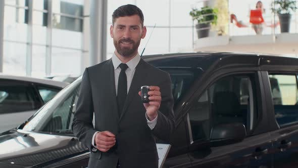 Thumbnail for Professional Car Salesman Smiling Happily Holding Car Keys Standing in Front of New Cars