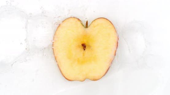 Thumbnail for On a White Background, Sliced Apple Slices Are Sprinkled with Water.