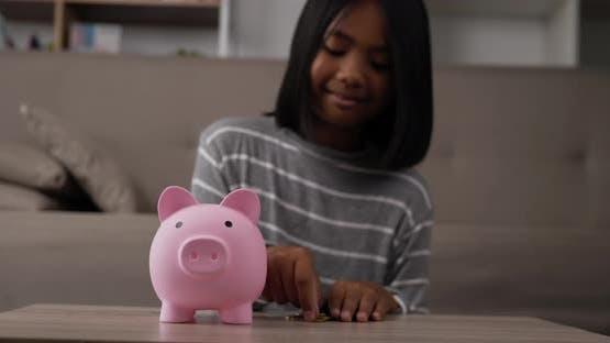 Girl putting coins into piggy bank
