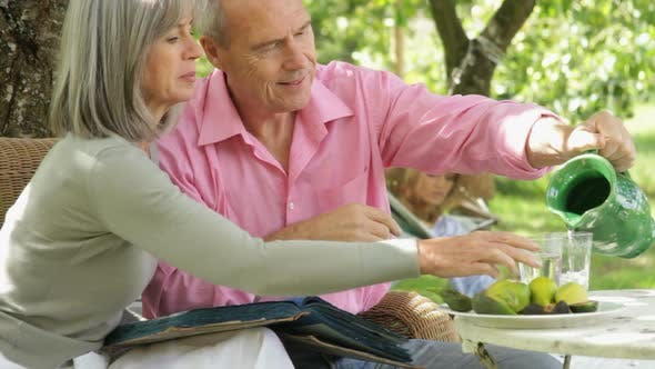 Thumbnail for Mature couple in garden eating and looking at photo album memories