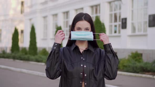 Woman Puts on a Protective Mask.