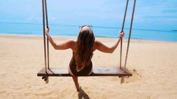 Thumbnail for A Young Woman in Green Swimming Suit Swinging on a Swings on the Beach and Having a Rest
