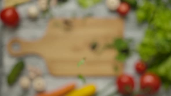 Thumbnail for Parsley and Basil Leaves Falling on Chopping Board