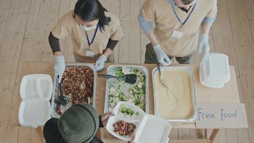 Top-View of Volunteers Giving Food to Needy People