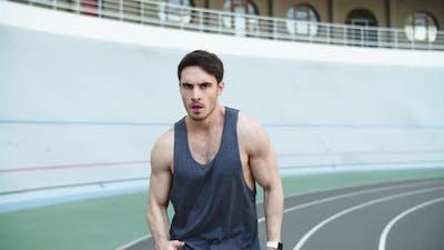Male Runner Running at Modern Track. Sport Man Running on Racetrack