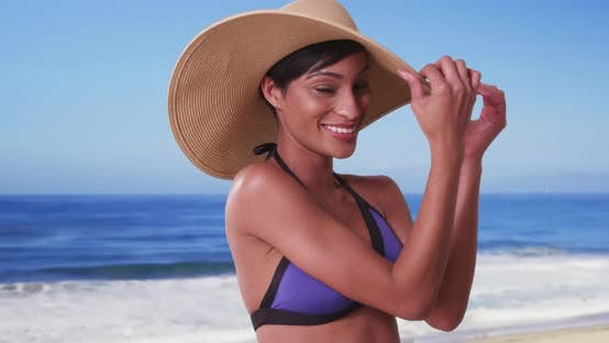 Thumbnail for Beautiful black woman with sunhat on the beach smiling and playing with hat