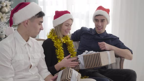 Thumbnail for Portrait of Beautiful Positive Girl Receiving Christmas Present From Twin Brothers. Adult Men